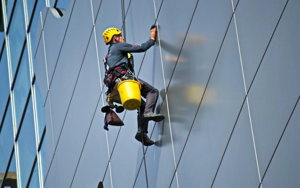 vinduespudser med spand og hjelm hænger i reb på skyskraber